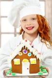 Criança com a casa de pão-de-espécie no Natal como o cozinheiro chefe Fotografia de Stock Royalty Free