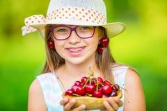 Criança com cerejas Menina com cerejas frescas Cintas e vidros vestindo dos dentes da menina loura caucasiano bonito nova fotografia de stock royalty free