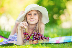 Criança com cerejas Menina com cerejas frescas Retrato de uma moça de sorriso com a bacia completa de cerejas frescas foto de stock royalty free