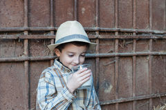 A criança com chapéu está bebendo um vidro do leite fresco Fotos de Stock