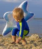 Criança com dois anos que joga perto da água fotos de stock royalty free