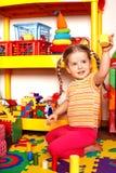 Criança com enigma e bloco de madeira no quarto do jogo. Fotografia de Stock