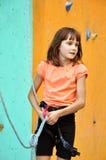 Criança com equipamento de escalada contra a parede do treinamento Fotografia de Stock