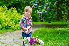Criança com flores lilás Imagens de Stock Royalty Free