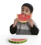 Criança com fome que come uma fatia da melancia Fotos de Stock Royalty Free