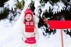 Criança com letra a Santa na caixa postal do Natal na neve Imagem de Stock