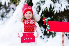 Criança com letra a Santa na caixa postal do Natal na neve Fotos de Stock Royalty Free