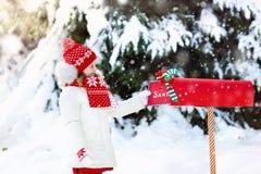 Criança com letra a Santa na caixa postal do Natal na neve Fotos de Stock