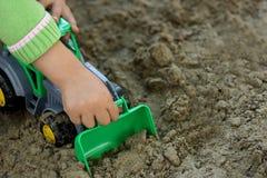 Criança com máquina escavadora verde Foto de Stock