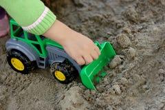 Criança com máquina escavadora verde Imagens de Stock