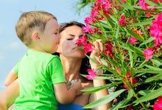 Criança com a mãe que cheira flores cor-de-rosa Fotografia de Stock