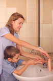 Criança com mãos da lavagem do mum Imagem de Stock