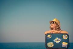 Criança com a mala de viagem do vintage em férias de verão Imagens de Stock