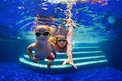 Criança com mergulho da mãe na piscina fotografia de stock royalty free