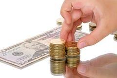Criança com moedas e dólares Fotografia de Stock