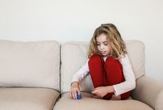 Criança com o autismo que empilha brinquedos no sofá fotografia de stock royalty free