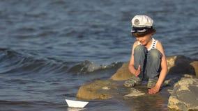 Criança com o barco de papel na água na praia A criança do rapaz pequeno põe o navio de papel sobre a superfície do mar Navigação video estoque