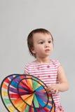 Criança com o brinquedo colorido do moinho de vento Imagens de Stock