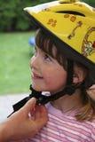 Criança com o capacete da bicicleta no amarelo Imagem de Stock Royalty Free