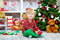 Criança com o carro do brinquedo pela árvore de Natal Foto de Stock Royalty Free