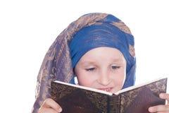 A criança com o livro em uma lição imagens de stock
