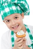 Criança com o queque da terra arrendada do chapéu do cozinheiro chefe Imagens de Stock Royalty Free