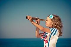 Criança com o telescópio pequeno do vintage em férias de verão Imagens de Stock Royalty Free