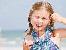 Criança com os óculos de sol na praia imagens de stock
