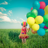 Criança com os balões do brinquedo no campo da mola Fotos de Stock Royalty Free