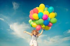 Criança com os balões do brinquedo no campo da mola Imagens de Stock