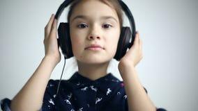Criança com os fones de ouvido que dançam no fundo do estúdio