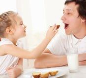 A criança com pai tem um pequeno almoço Fotos de Stock