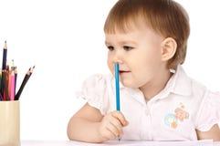 A criança com pastel azul pensa sobre desenhos Fotos de Stock