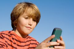 Criança com pilha ou o telefone móvel Fotografia de Stock