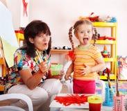 Criança com pinturas da tração do professor no playroom. imagem de stock