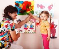 Criança com pinturas da tração do professor no playroom. fotos de stock