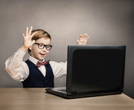 Criança com portátil, Little Boy nos vidros surpreendida olhando o computador Fotos de Stock