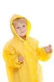 Criança com raincoat amarelo Fotos de Stock Royalty Free