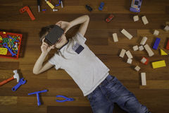 Criança com realidade 3D virtual, vidros do cartão de VR que encontram-se no assoalho de madeira Muitos brinquedos em torno dele Fotos de Stock