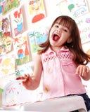 Criança com retrato e escova no quarto do jogo. Fotos de Stock