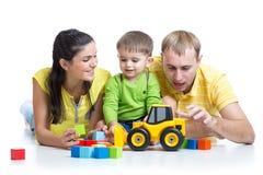 Criança com seus brinquedos dos blocos de apartamentos do jogo dos pais Foto de Stock Royalty Free