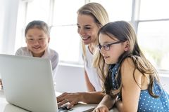 Criança com tabuleta e laptop da tecnologia no professor da sala de aula no fundo imagens de stock