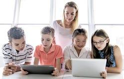 Criança com tabuleta e laptop da tecnologia no professor da sala de aula no fundo foto de stock royalty free