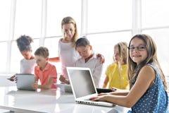 Criança com tabuleta e laptop da tecnologia no professor da sala de aula no fundo foto de stock