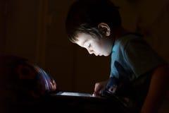 Criança com a tabuleta na obscuridade