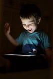 Criança com a tabuleta na obscuridade Imagens de Stock