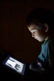 Criança com a tabuleta na obscuridade imagens de stock royalty free