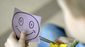 A criança com tesouras corta do smiley de papel filme