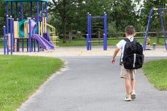 Criança com trouxa e livro da escola que anda no parque imagem de stock