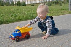 Criança com um caminhão do brinquedo Fotografia de Stock Royalty Free